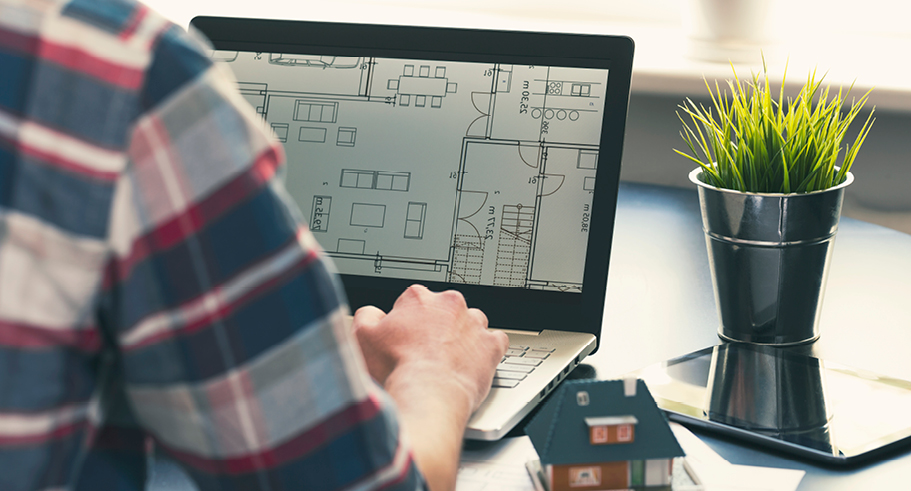 Man looking at building plans on his laptop