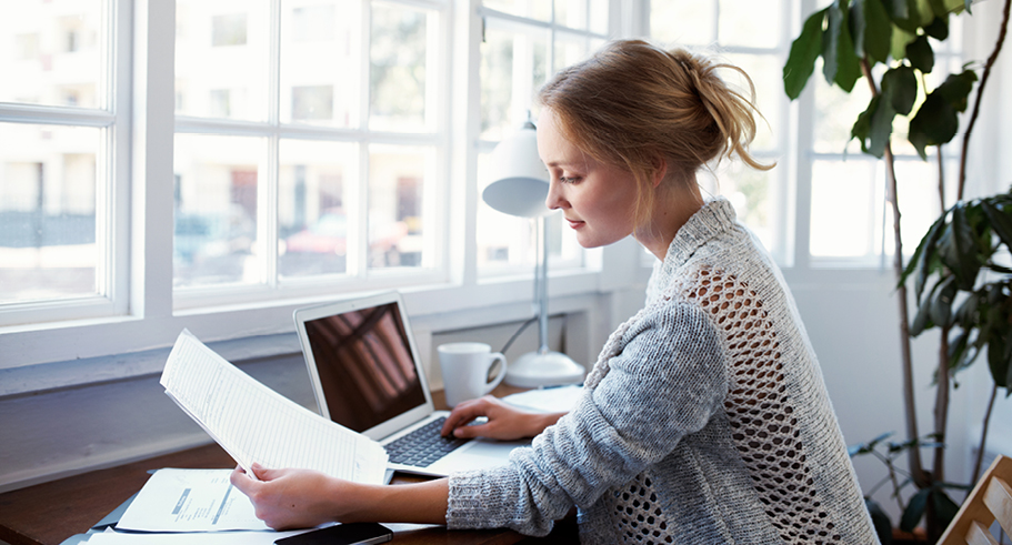 Young lady paying bills online at desk